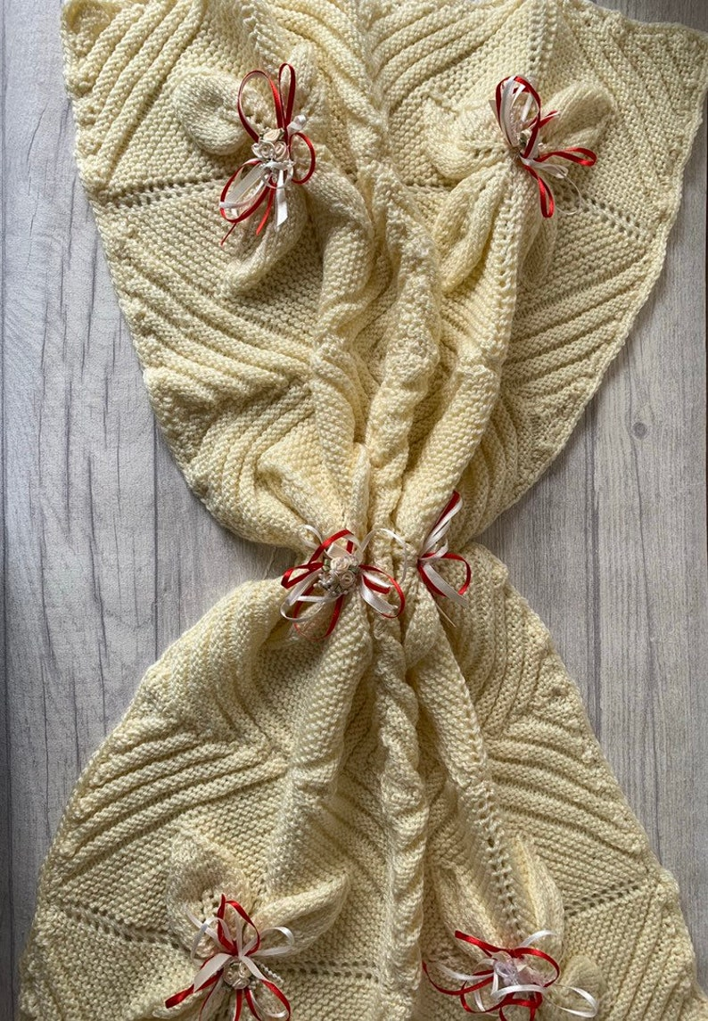 Cream hand knit baby blanket with red ribbons
