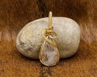 Brass & Astrophylite in Quartz pendant
