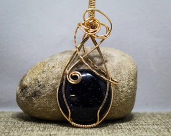 Bronze wrapped blue goldstone pendant