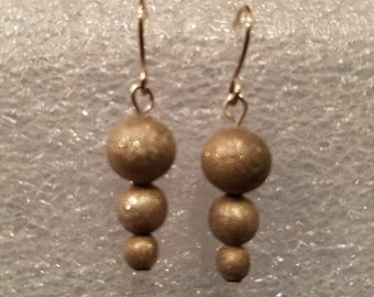 Dangle earrings featuring graduated size sterling silver rounds with stardust finish