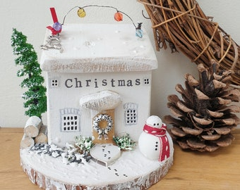 Christmas cottage on log slice with frosty the snowman