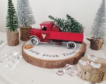 Red Christmas tree delivery truck with Snowy Farm fresh trees log slice plinth .. ready to dispatch