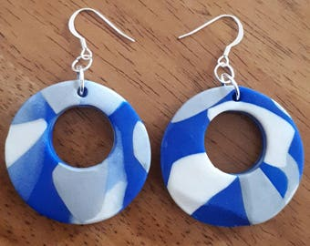 Polymer clay dangle earrings. Blue, silver and white clay in a donut shape. Have used silver tone findings.