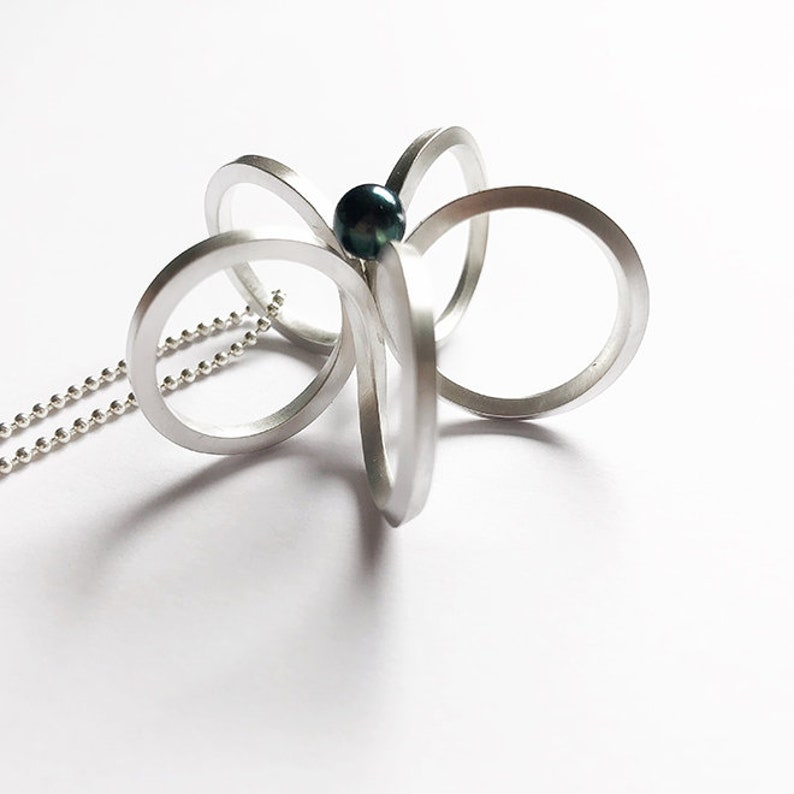 Long silver necklace with a special flower pendantscandinaviangraphic