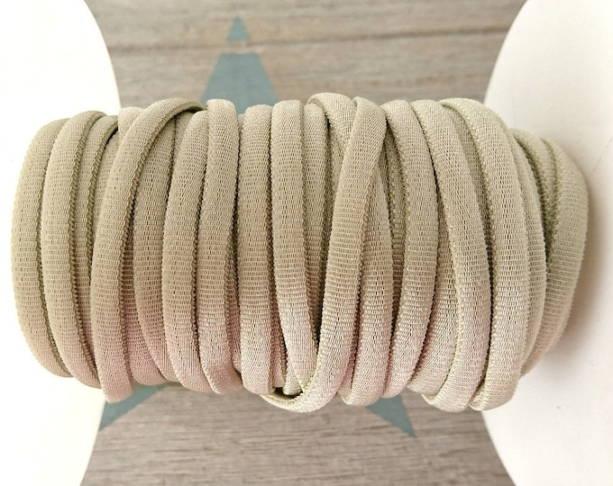 1 meter of 4.5mm beige elastic tubular tape.