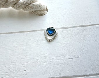 1 Triangle pendant with dark blue resin. Measures 15x14mm.