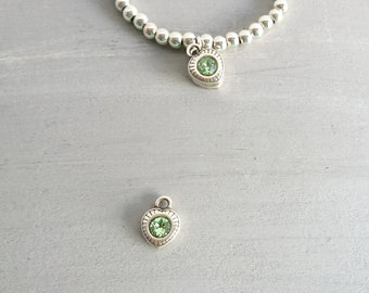 Heart pendant with green Swarovski crystal. 15x11mm. 1 unit. High quality silver zamak metal.
