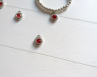Heart pendant with red swarovski crystal. 15x11mm. 1 unit. High quality silver zamak metal.