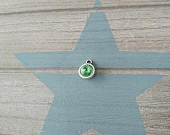 1 Round pendant with green swarovski. 14x11mm High quality silver zamak metal.