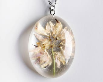 Oval shaped resin pendant with dry flower-