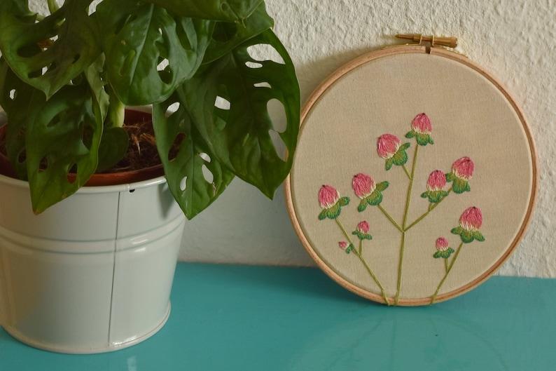Borduurwerk voor aan de muur met roze besjes planten. image 0