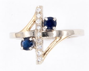 Stunning one-of-a-kind geometric engagement / cocktail ring, pave set with 9 brilliant diamonds and graced with two royal blue Sapphires.