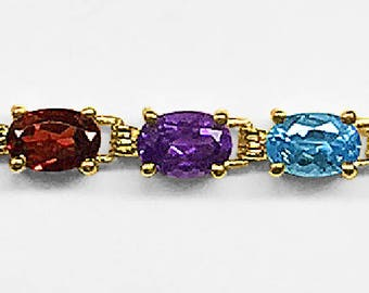 Vintage English 9K solid Yellow Gold Line Bracelet prong set with 21 of the finest Blue Topaz, Garnets and Amethysts; measuring 7 1/2 inches
