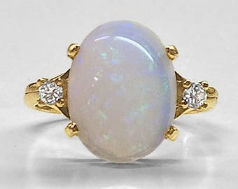 Spectacular vintage prong set oval Australian Opal Ring in 18K Yellow Gold flanked on each side by a fine quality brilliant cut Diamond