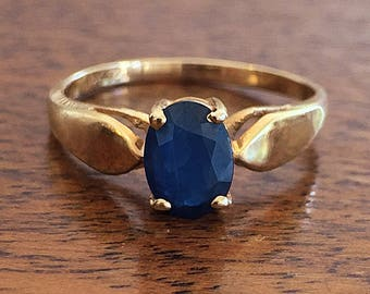 14K Yellow Gold understated prong set Oval faceted Dark Blue Sapphire Solitaire Ring circa 1970's with deco-like feel