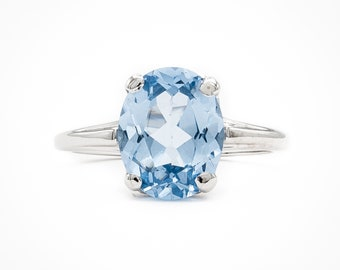 Lively oval faceted Sky Blue Topaz prong set Solitaire ring in 14K White Gold. Utter elegant everyday simplicity.