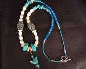 Ceramic bird on a necklace of turquoise beads, metal beads, glass beads, shell beads and bone carved beads with a sterling silver clasp.