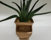 Artificial Aloe plant in copper painted ceramic container with small tan rocks glued in.