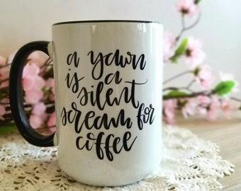 A yawn . Silent scream for Coffee . Need Coffee . Ceramic Mug