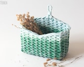 Small green-blue wall hanging storage basket with a loop