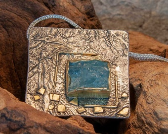 Hand-forged silver pendant with gold details and aquamarine in gold frame