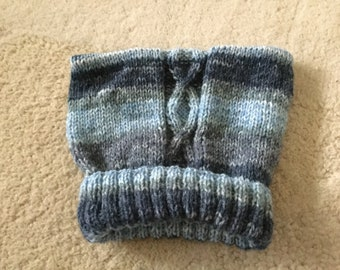 Hand knitted pull on teabag baby hat with cable pattern, variegated shades of blue