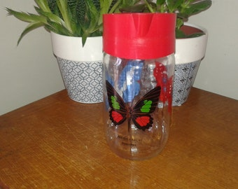Vintage glass pitcher and plastic butterfly decor