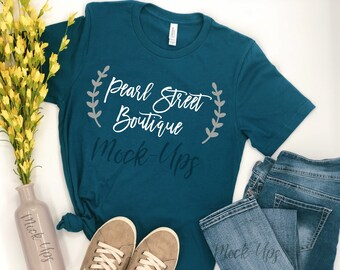 Download Free Mockup Deep Teal Bella Canvas Unisex Shirt, White Background, Flat-Lay, Flower Vase, Converse Tennis Style Shoes, Blue Jeans, Summer Spring PSD Template