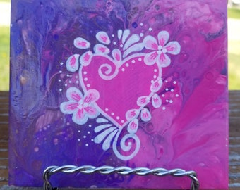 Hand-painted tile with poured, fluid art background and swirly floral heart