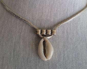 leather pendant silver color with a holes object +shell.