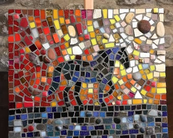 Mosaic horse silhouetted against the sunset, in blue, black, red and orange