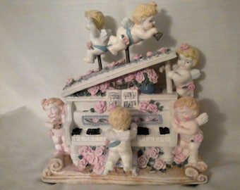 "Vintage Cherubs Playing The Piano. 7"" long, 7"" high, 5 1/2"" deep. made of resin."