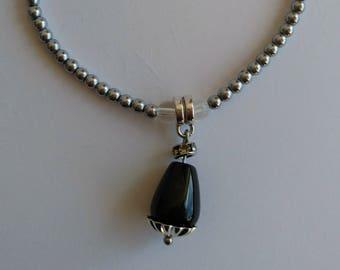 Elastic bracelet in hematite, onyx pendant