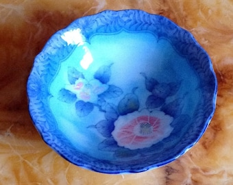 Small chinese ring dish flower design inscribed with chinese writing.