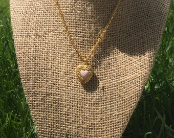 Gold heart pendant necklace with pink heart on top.