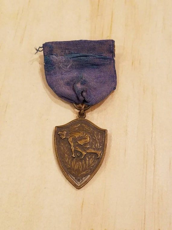 Gold color Vintage track and field medal pin intact blue ribbon Antique sports medal pin with blue ribbon.