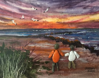 Pebble art painting of a couple walking hand in hand on the beach at sunset