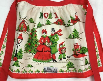 """Vintage Christmas Half Apron, Parisian Prints with Original Paper Label, """"Noel"""" Caroling in the Winter Snow! Printed as if  x-Stitch, 1960's"""