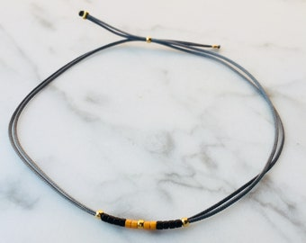 Grey bracelet with golden accents