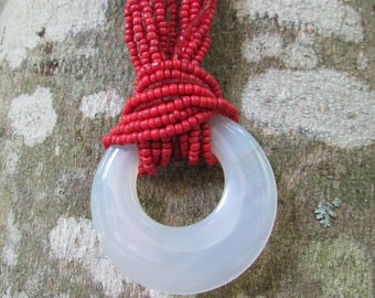 Round translucent pendant with red beaded necklace