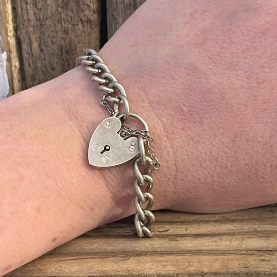 A vintage sterling silver curb link bracelet with a fully hallmarked for 1965 padlock heart clasp