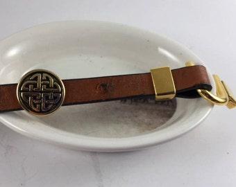 Gold Celtic disk and hook closure on brown ostrich leather.