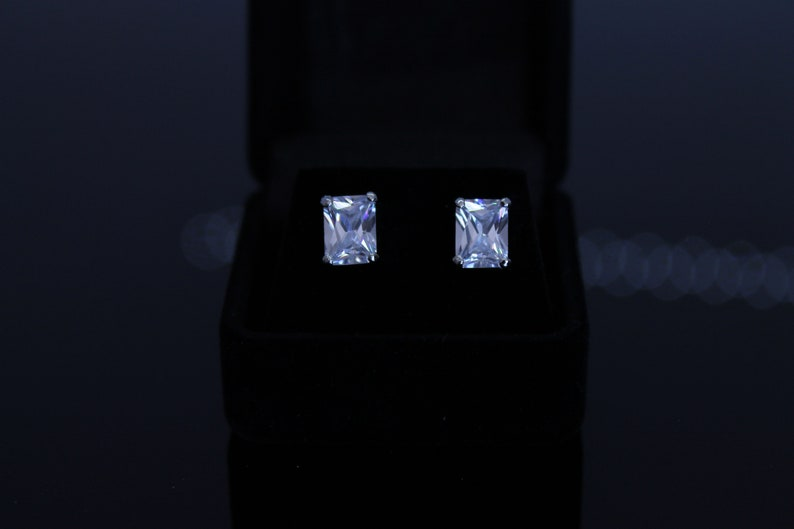 Rhodium plated black velvet box included cubic zirconia pierced earrings Available in 6 different shapes. 8X4 mm clear emerald cut
