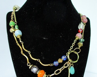 Unique, long multicolored wrap necklace using an assortment of gold tone chains