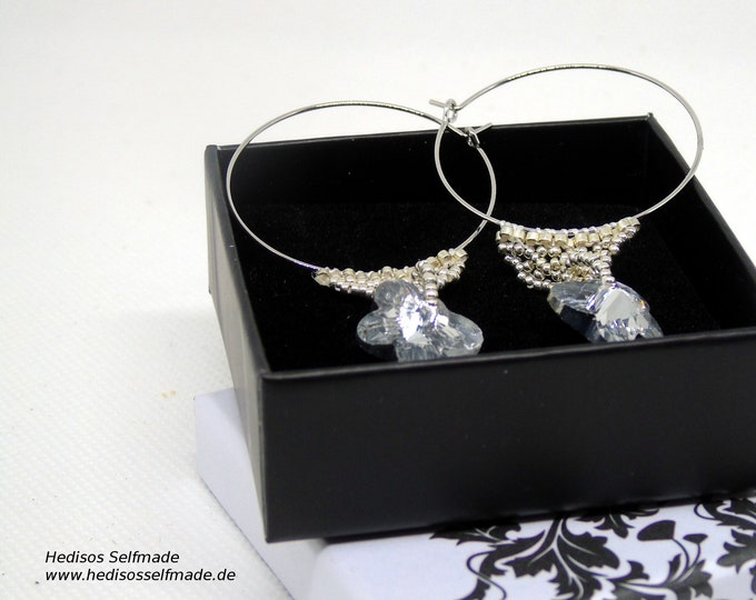 Silver earrings threaded with a Swarovski butterfly using mesh technology