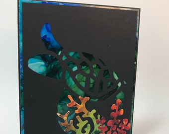 Turtle silouette set on multi colored background with black face, marine, sealife, coral