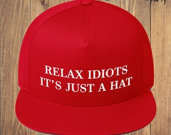 1082e24fa83ca Relax Idiots It s Just A Hat (Embroidered Snapback Cap) Funny MAGA Red  Trump Hat Parody