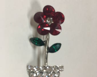 Red crystal flower brooch on silver tone.