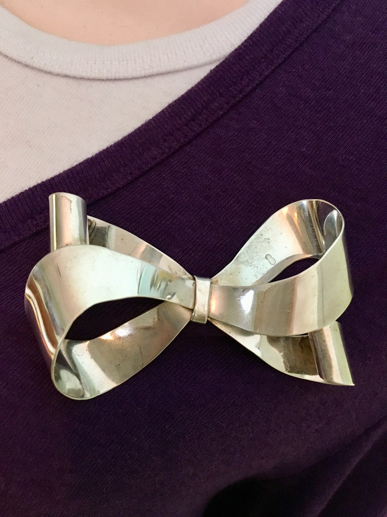 Large sterling silver bow brooch with curling ribbon ends