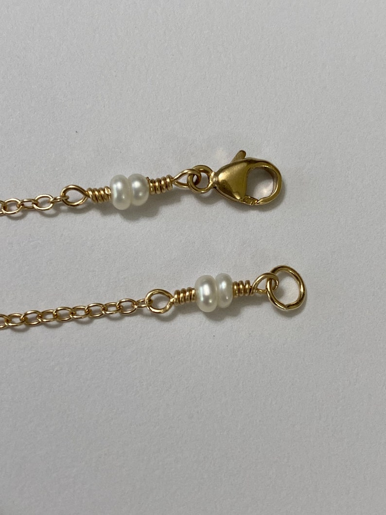 Natural Pearl and Shell necklace on Gold chain.